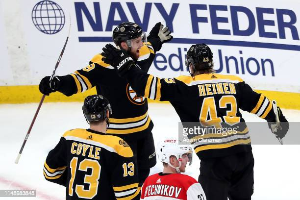 Matt Grzelcyk of the Boston Bruins celebrates with teammates after scoring a goal during the first period against the Carolina Hurricanes in Game Two...