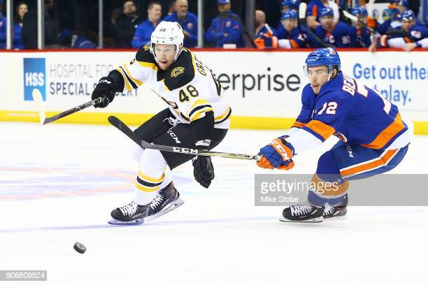 Matt Grzelcyk of the Boston Bruins chases down a loose puck while fending off pressure from Anthony Beauvillier of the New York Islanders during the...