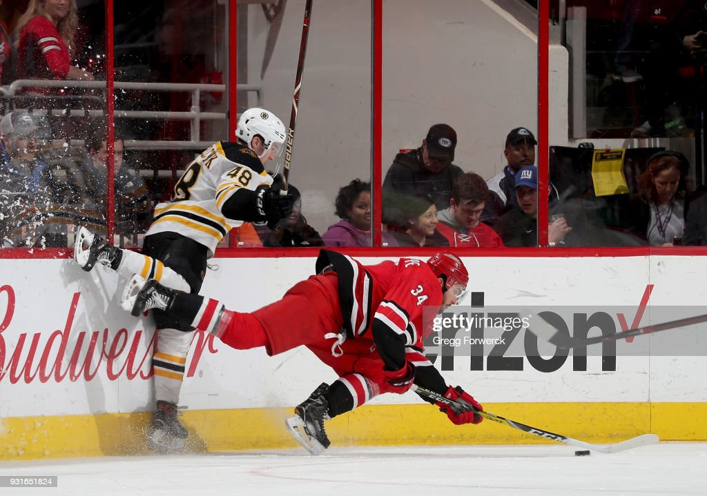 Matt Grzelcyk #48 of the Boston Bruins checks Phillip Di Giuseppe #34 of the Carolina Hurricanes along the boards during an NHL game on March 13, 2018 at PNC Arena in Raleigh, North Carolina.