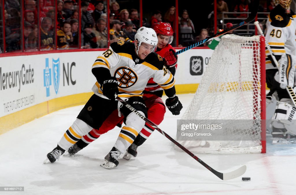 Matt Grzelcyk #48 of the Boston Bruins controls the puck away from Sebastian Aho #20 during an NHL game on March 13, 2018 at PNC Arena in Raleigh, North Carolina.