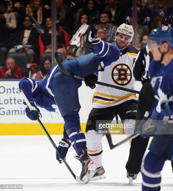 Matt Grzelcyk of the Boston Bruins flips William Nylander of the Toronto Maple Leafs during the first period at the Scotiabank Arena on November 15,...