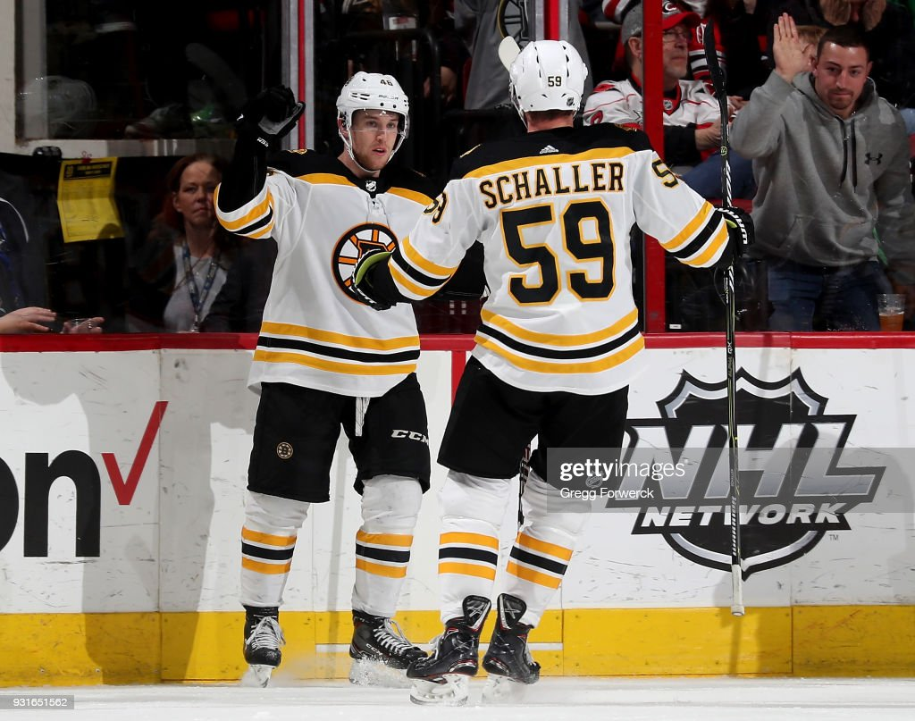 Matt Grzelcyk #48 of the Boston Bruins is congratulated by teammate Tim Schaller #59 after scoring a goal during an NHL game against the Carolina Hurricanes on March 13, 2018 at PNC Arena in Raleigh, North Carolina.