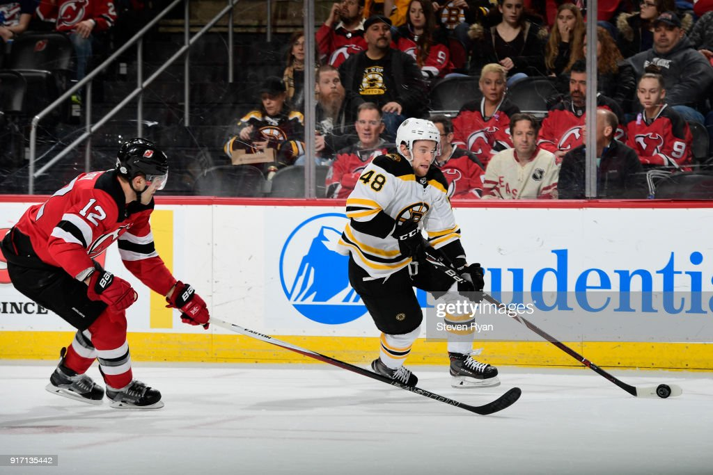 Matt Grzelcyk #48 of the Boston Bruins is pursued by Ben Lovejoy #12 of the New Jersey Devils at Prudential Center on February 11, 2018 in Newark, New Jersey. The Boston Bruins defeated the New Jersey Devils 5-3.