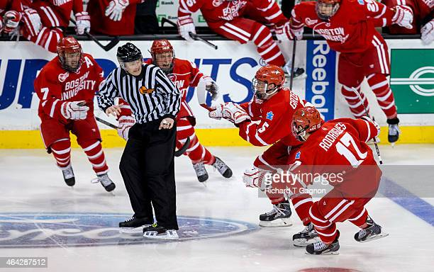 Matt Grzelcyk of the Boston University Terriers celebrates his overtime winning goal against the Northeastern Huskies with teammates Evan Rodrigues...