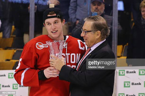Matt Grzelcyk of the Boston University Terriers is awarded the MVP trophy after the Terriers defeat the Northeastern Huskies 4-3 in overtime during...