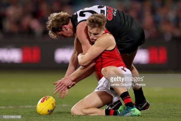 Matt Guelfi of the Bombers is tackled by Jack Watts of the Power during the 2018 AFL round 23 match between the Port Adelaide Power and the Essendon...