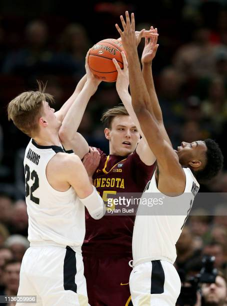 Matt Haarms and Aaron Wheeler of the Purdue Boilermakers pressure Matz Stockman of the Minnesota Golden Gophers in the first half during the...
