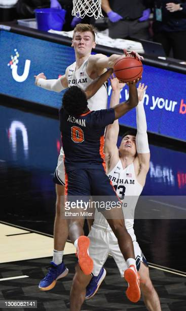 Matt Haarms of the Brigham Young Cougars blocks a shot by Sedrick Altman of the Pepperdine Waves as Alex Barcello of the Cougars defends during the...