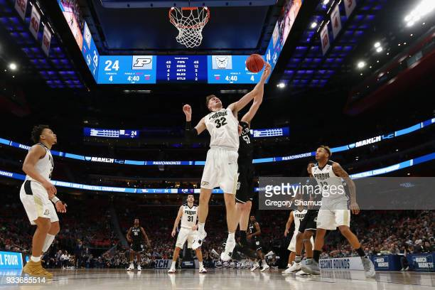 Matt Haarms of the Purdue Boilermakers battles for a rebound with Nate Fowler of the Butler Bulldogs during the first half in the second round of the...