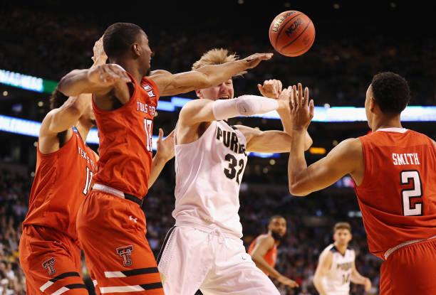 Matt Haarms of the Purdue Boilermakers battles for the ball with Keenan Evans and Zhaire Smith of the Texas Tech Red Raiders during the first half in...