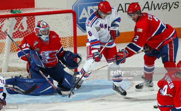 Matt Halischuk of the Kitchener Rangers tries to tip an incoming shot between Dustin Tokarski and Jared Cowen of the Spokane Chiefs in a Memorial Cup...