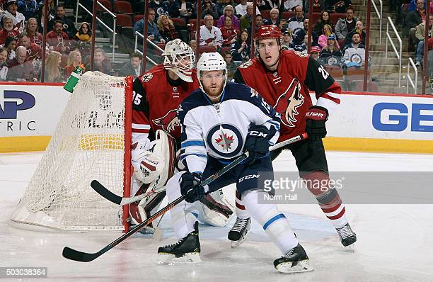 Matt Halischuk of the Winnipeg Jets and Michael Stone of the Arizona Coyotes battle for position in front of goaltender Louis Domigue of the Coyotes...
