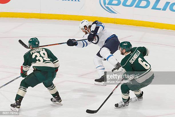 Matt Halischuk of the Winnipeg Jets shoots the puck with Nate Prosser and Marco Scandella of the Minnesota Wild defending during the game on January...