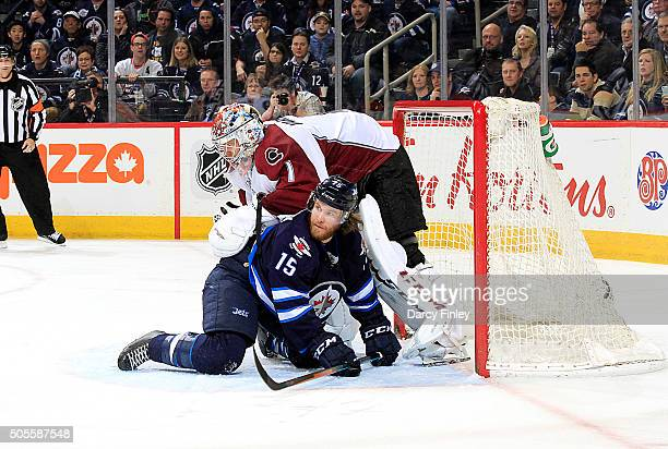 Matt Halischuk of the Winnipeg Jets slides into goaltender Semyon Varlamov of the Colorado Avalanche during third period action at the MTS Centre on...