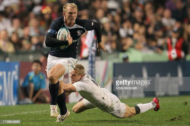 Matt Hawkins of the USA breaks the tackle of Nick Royle of England during day two of the IRB Sevens at Hong Kong Stadium on March 26, 2011 in So Kon...