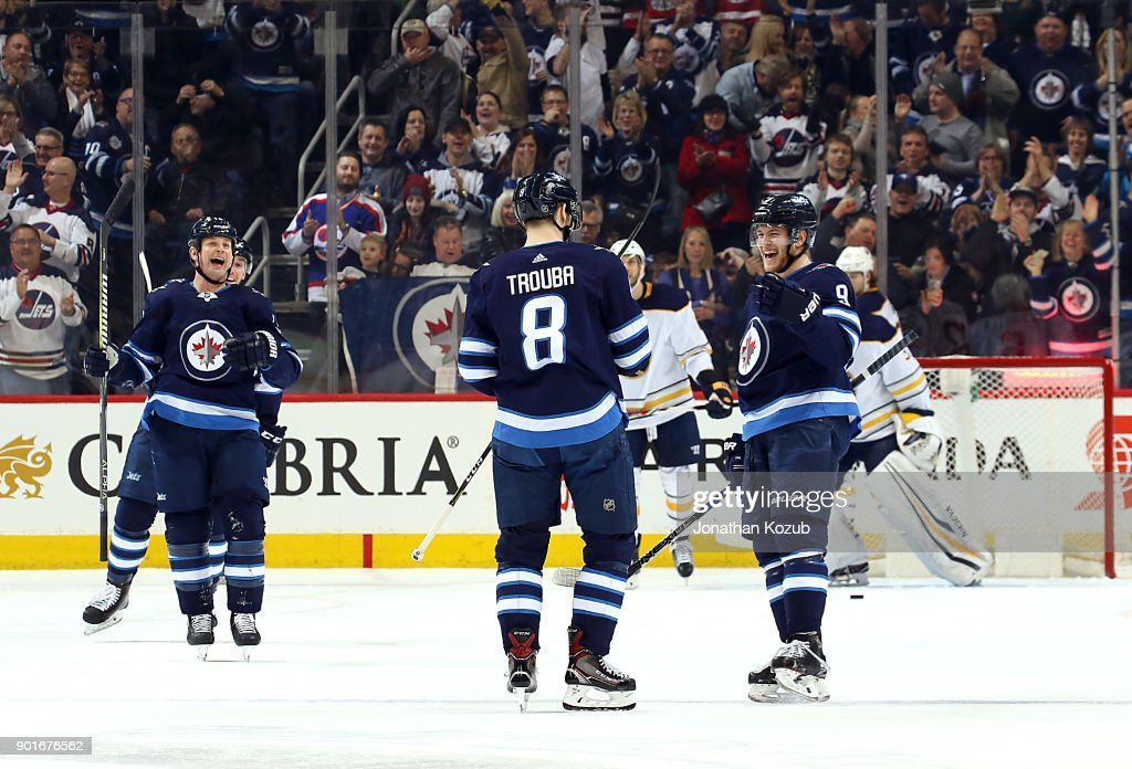 Matt Hendricks #15 and Andrew Copp #9 of the Winnipeg Jets are all smiles as they join Jacob Trouba #8 to celebrate his first period goal against the Buffalo Sabres at the Bell MTS Place on January 5, 2018 in Winnipeg, Manitoba, Canada.