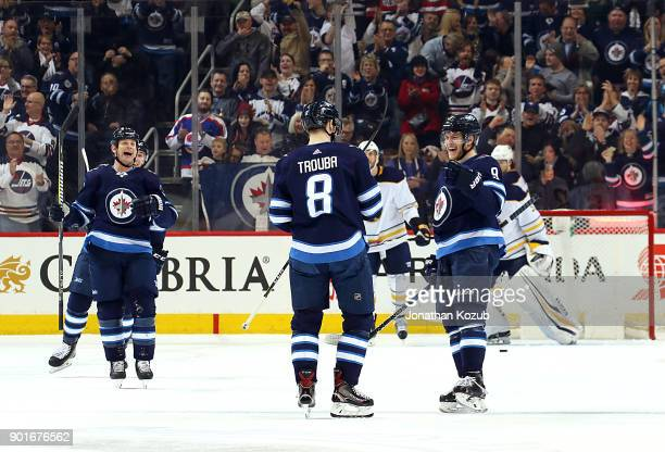 Matt Hendricks and Andrew Copp of the Winnipeg Jets are all smiles as they join Jacob Trouba to celebrate his first period goal against the Buffalo...