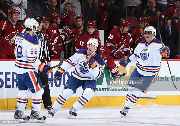Matt Hendricks and David Perron of the Edmonton Oilers congratulate Sam Gagner after Gagner scored the game winning shoot-out goal against the...