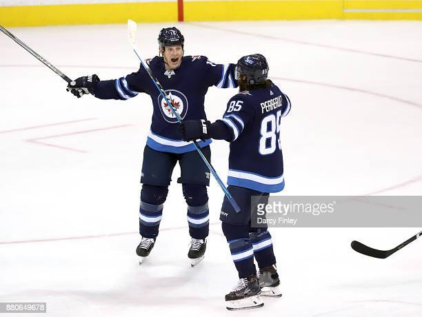 Matt Hendricks and Mathieu Perreault of the Winnipeg Jets celebrate after scoring a second period goal against the Minnesota Wild at the Bell MTS...