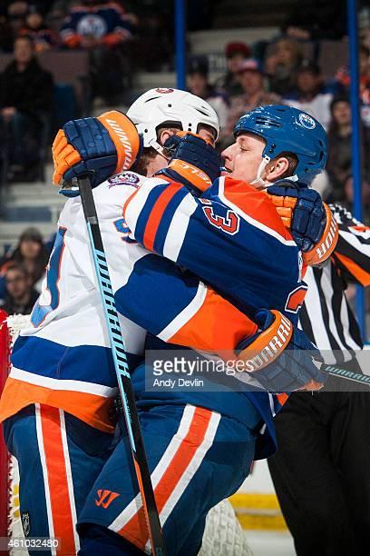 Matt Hendricks of the Edmonton Oilers battles against Casey Cizikas of the New York Islanders on January 4 2015 at Rexall Place in Edmonton Alberta...