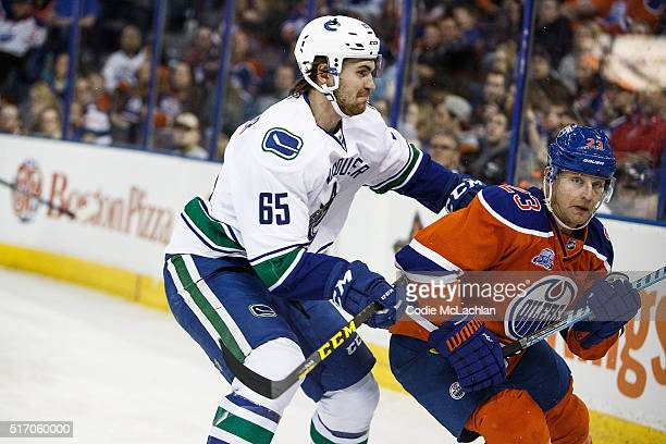 Matt Hendricks of the Edmonton Oilers is shoved by Alexandre Grenier of the Vancouver Canucks on March 18 2016 at Rexall Place in Edmonton Alberta...