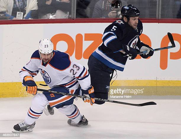 Matt Hendricks of the Edmonton Oilers trips up Mark Stuart of the Winnipeg Jets in first period action in an NHL game at the MTS Centre on January 18...