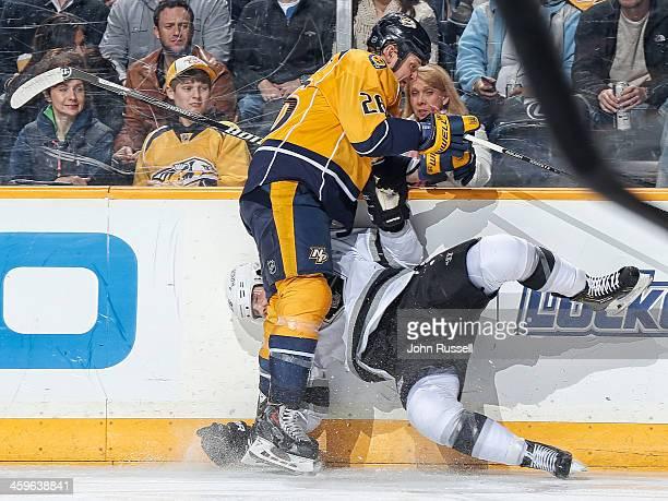 Matt Hendricks of the Nashville Predators checks Slava Voynov of the Los Angeles Kings into the boards at Bridgestone Arena on December 28 2013 in...