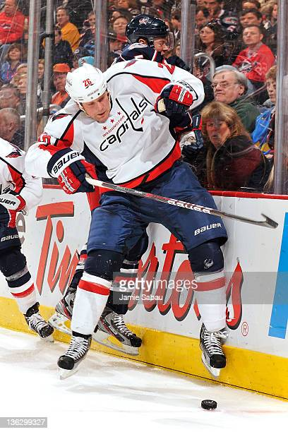 Matt Hendricks of the Washington Capitals checks Aaron Johnson of the Columbus Blue Jackets while chasing after a loose puck during the second period...