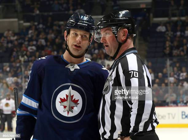 Matt Hendricks of the Winnipeg Jets chats with linesman Derek Nansen during a third period stoppage in play against the Chicago Blackhawks at the...