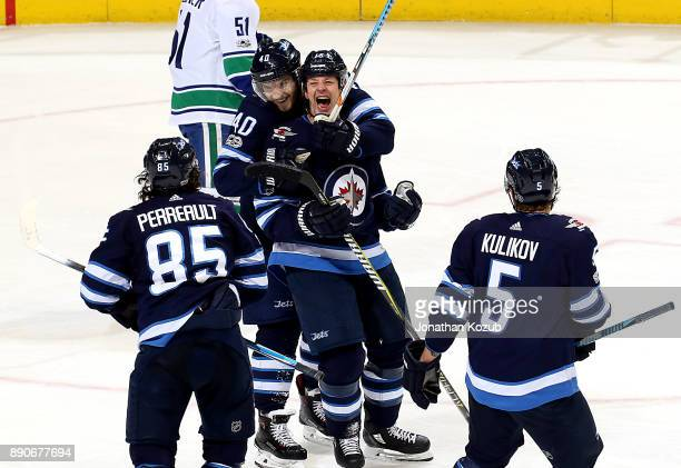 Matt Hendricks of the Winnipeg Jets is all smiles as he celebrates a third period goal against the Vancouver Canucks with teammates Mathieu Perreault...