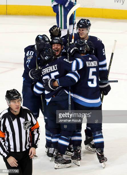 Matt Hendricks of the Winnipeg Jets is all smiles as he celebrates a third period goal against the Vancouver Canucks with teammates Joel Armia...