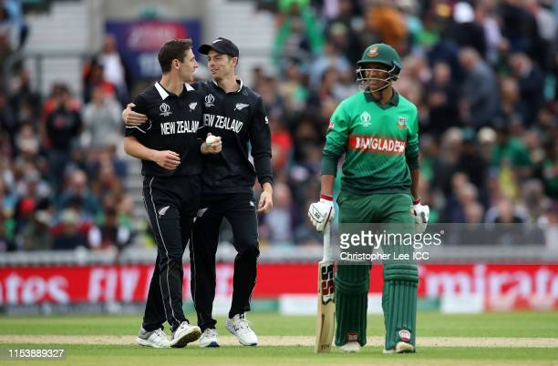 Matt Henry and Mitchell Santner of New Zealand celebrate the wicket of Mohammad Saifuddin of Bangladesh during the Group Stage match of the ICC...