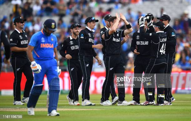 Matt Henry of New Zealand is congratulated by team mates after dismissing Rohit Sharma of India during resumption of the Semi-Final match of the ICC...