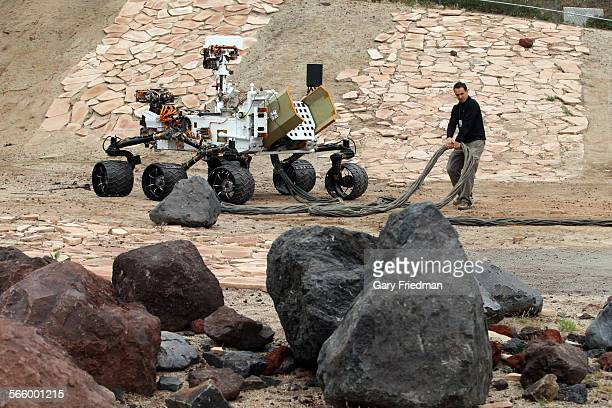 Matt Heverly moves power and communications tether which is used to power and command the Vehicle System Testbed rover at the Jet Propulsion...
