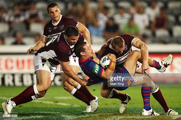 Matt Hilder of the Knights is tackled heavily during the round three NRL match between the Manly Warringah Sea Eagles and the Newcastle Knights at...