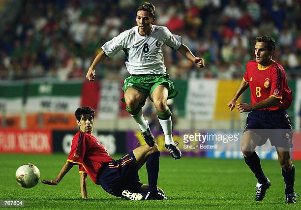 Matt Holland of the Republic of Ireland hurdles the tackle of Juan Carlos Valeron of Spain during the FIFA World Cup Finals 2002 Second Round match...