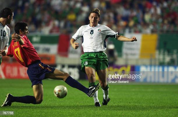 Matt Holland of the Republic of Ireland is tackled by Juan Carlos Valeron of Spain during the FIFA World Cup Finals 2002 Second Round match played at...