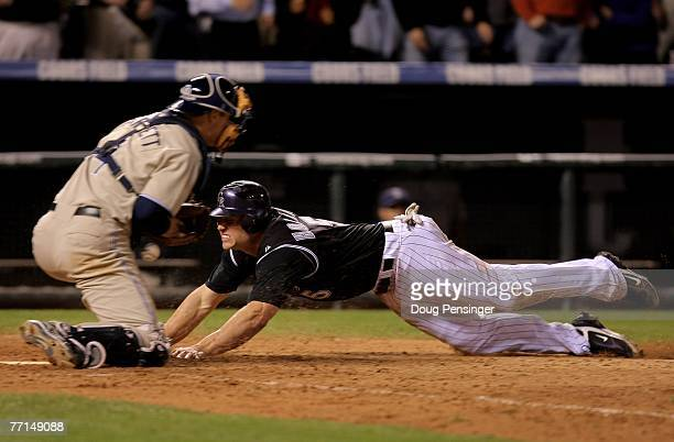 Matt Holliday of the Colorado Rockies dives home with the winning run on a base hit by Jamey Carroll as Michael Barrett of the San Diego Padres tries...