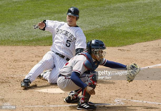 Matt Holliday of the Colorado Rockies slides home before catcher Johnny Estrada of the Atlanta Braves can make the tag on a double by pinch hitter...