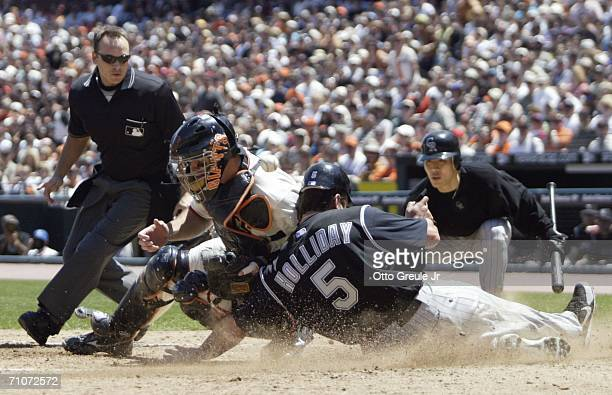 Matt Holliday of the Colorado Rockies slides home to score against catcher Mike Matheny of the San Francisco Giants in the fourth inning on May 28,...