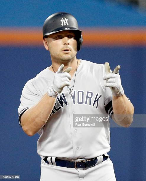 Matt Holliday of the New York Yankees points back to his dugout after hitting a double during an MLB baseball game against the Tampa Bay Rays on...