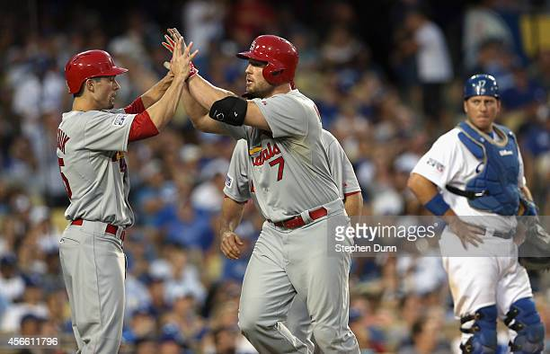 Matt Holliday of the St Louis Cardinals celebrates his three run homerun with teammates in the seventh inning during Game One of the National League...