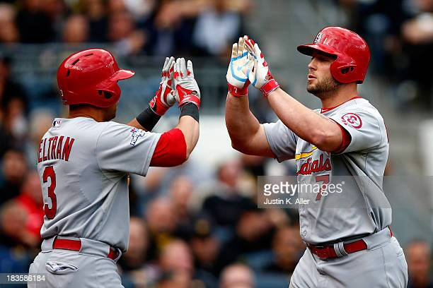 Matt Holliday of the St Louis Cardinals celebrates scoring a two run home run with teammates Carlos Beltran against Charlie Morton of the Pittsburgh...