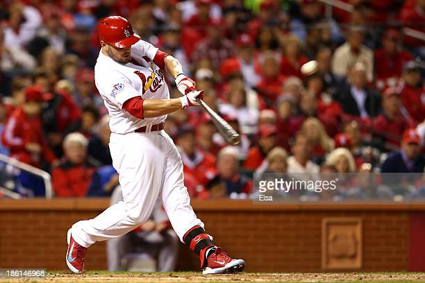 Matt Holliday of the St Louis Cardinals hits a solo home run in the fourth inning against the Boston Red Sox during Game Five of the 2013 World...