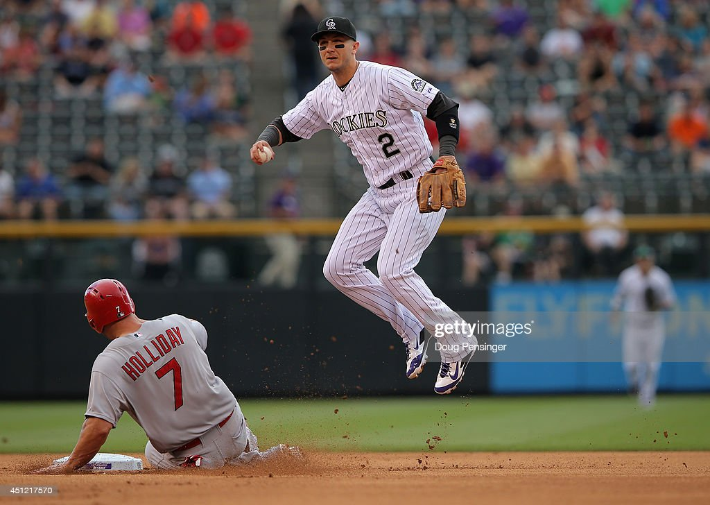 Matt Holliday #7 of the St. Louis Cardinals is forced out at second base by shortstop Troy Tulowitzki #2 of the Colorado Rockies and breaks up the double play attempt in the first inning at Coors Field on June 25, 2014 in Denver, Colorado.