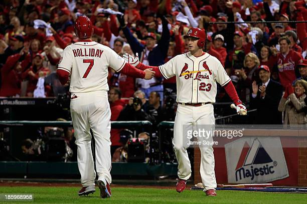 Matt Holliday of the St Louis Cardinals is greeted by David Freese after scoring on a single by Yadier Molina in the first inning against the Boston...