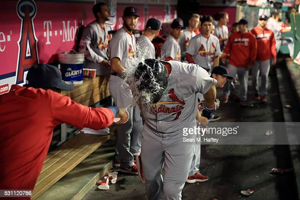 Matt Holliday of the St Louis Cardinals is splashed with water by Carlos Martinez of the St Louis Cardinals in the dugout after hitting a solo...