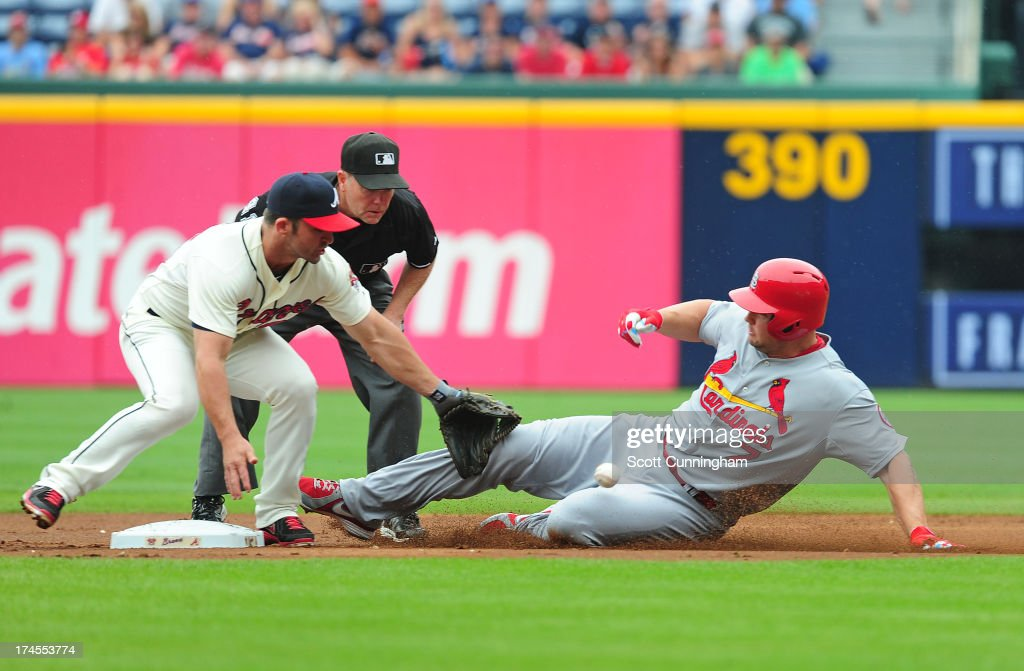Matt Holliday #7 of the St. Louis Cardinals slides in to second base for a first inning double against Dan Uggla #26 of the Atlanta Braves at Turner Field on July 27, 2013 in Atlanta, Georgia.