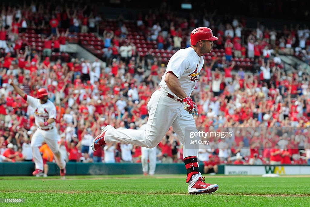 Matt Holliday #7 of the St. Louis Cardinals watches his walk-off, RBI single as Matt Carpenter #13 scores in the 12th inning against the Pittsburgh Pirates at Busch Stadium on August 15, 2013 in St. Louis, Missouri. Cardinals won 6-5 in twelve innings.