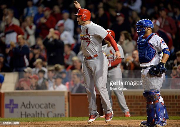 Matt Holliday of the St. Louis Cardinals waves home teammate Jhonny Peralta as catcher Welington Castillo of the Chicago Cubs stands on the field...
